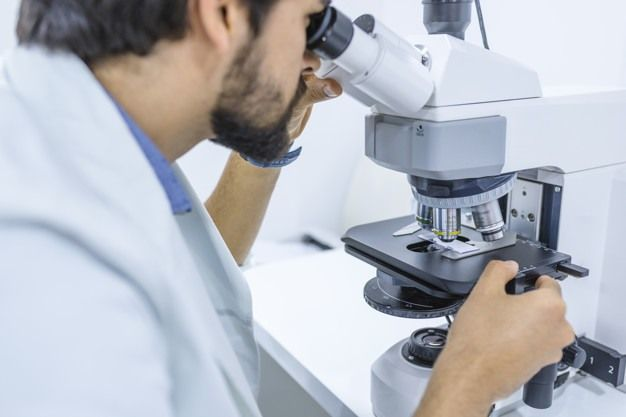 Scientist looking through a microscope in a laboratory. Gene expert. Attractive serious researcher wearing a uniform and looking into a microscope while making an analysis