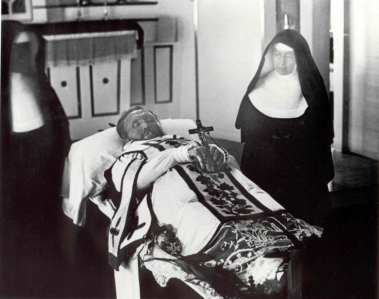 1280px-Father_Damien_on_his_funeral_bier_with_Mother_Marianne_Cope_by_his_side